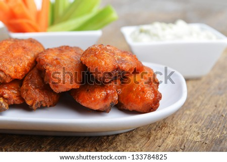 chicken wings with celery and carrot on wooden background