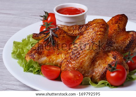 Chicken wings with cherry tomatoes, lettuce and sauce closeup - stock photo