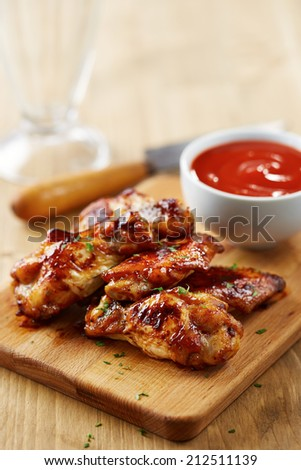 Chicken wings with sriracha sauce on wooden table - stock photo