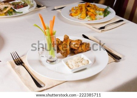Chicken Wings with Vegetables and Dip on Plate on Restaurant Table - stock photo