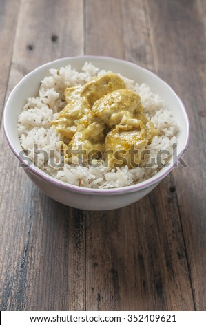 Chicken with curry sauce accompanied by rice basmati