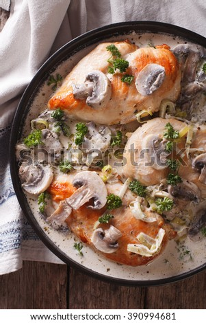 Chicken with mushroom sauce close-up on a plate on the table. vertical view from above - stock photo