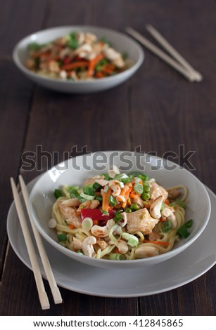 Chicken with noodles and cashew on wooden table - stock photo