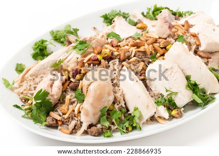 Chicken with spiced rice and nuts, garnished with parsley, a Lebanese celebratory dish. - stock photo