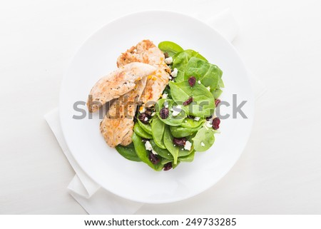 Chicken with spinach salad on white wooden background top view. Healthy food. - stock photo