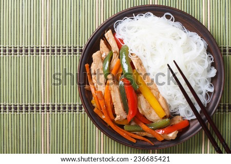 Chicken with vegetables and rice noodles. top view of a horizontal  - stock photo