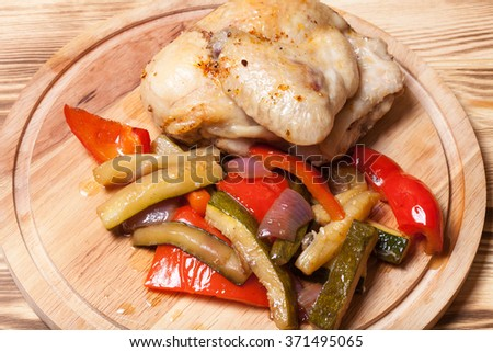 Chicken with vegetables served on round cutting board on burned wooden table. - stock photo