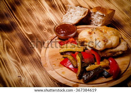 Chicken with vegetables served on round cutting board on burned wooden table. Toned. - stock photo