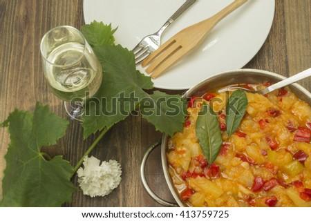 chicken with zucchini,zucchini stew with chicken,glass of wine and vine leaf  - stock photo