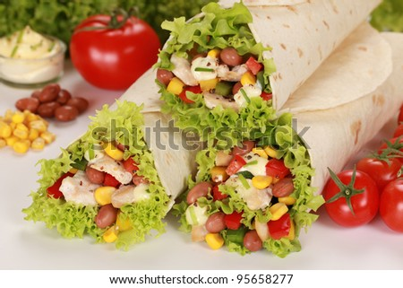 Chicken wrap sandwiches filled with beans, lettuce and corn