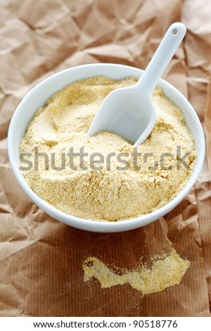Chickpea flour in a bowl with a shovel on paper.