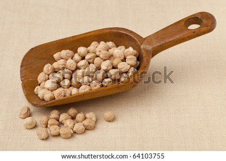 chickpea (garbanzo bean) on a rustic, wooden scoop against tablecloth - stock photo