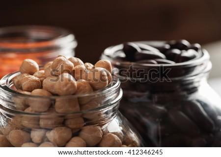 Chickpeas and red beans in glass jars macro shot, selective focus - stock photo
