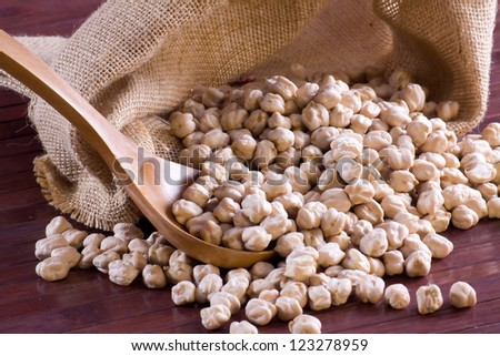 Chickpeas in a wooden spoon and bag - stock photo