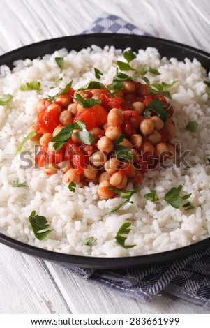 Chickpeas in tomato sauce with rice in a dish close-up. vertical