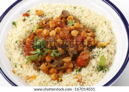 Chickpeas or garbanzo beans and quartered button mushrooms cooked in a spicy tomato and onion sauce and served with couscous mixed with parsley and dried apricots, Moroccan style, served in a bowl - stock photo