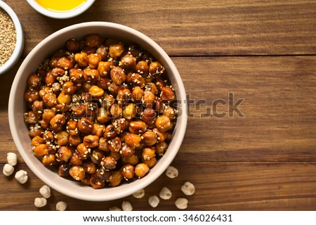 Chickpeas roasted with sesame and honey, photographed overhead on wood with natural light - stock photo