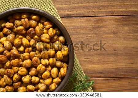 Chickpeas roasted with thyme, oregano, salt and pepper, photographed overhead on wood with natural light (Selective Focus, Focus on the chickpeas) - stock photo