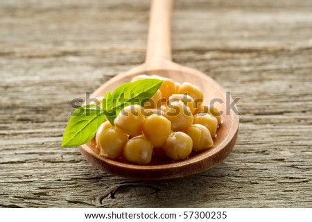 chickpeas with basil over spoon - stock photo