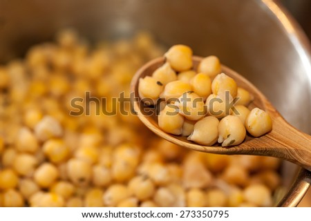 Chickpeas with thyme on a wooden spoon against chickpeas boiling in a steel sauce pan - stock photo