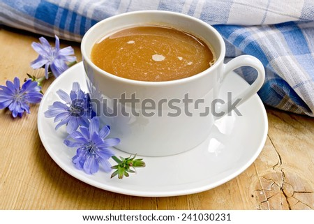 Chicory drink in a white cup with a flower napkin on a wooden boards background - stock photo