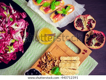 Chicory salad with appetizers set: prosciutto, pomegranate, olives, nuts, cheese and bruschetta on dark wooden background. Italian food. Top view, horizontal - stock photo