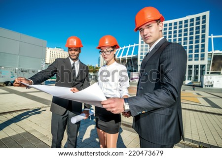 Chief architect. Three confident business architect in protective helmet standing on the site and keep the blueprints in the hands of
