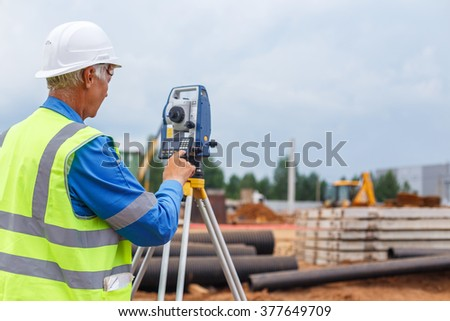 Chief Engineer in the construction helmet makes measurements using surveying equipment