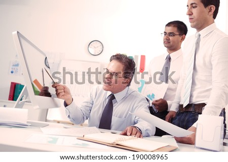 Chief explaining something to his employees pointing at the screen of the computer - stock photo