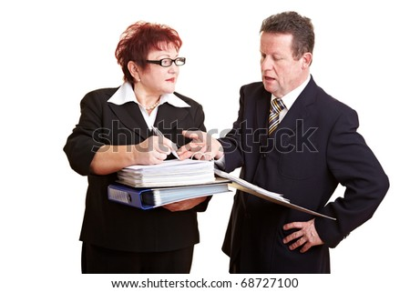 Chief giving orders to an elderly employee with files