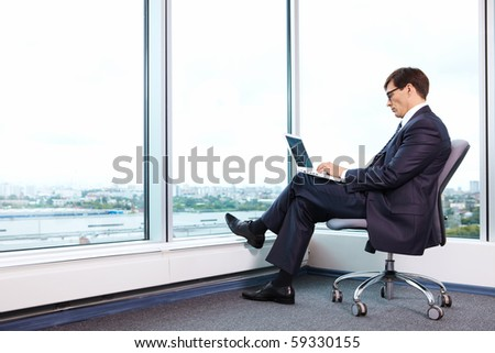 Chief works with a laptop in the office on the background of a large window - stock photo