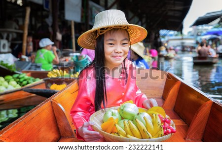 Chikd sit on the boat and hold the fruit basket in Traditional floating market , Thailand. - stock photo