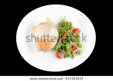 Chiken with vegetables on white plate on black background - stock photo