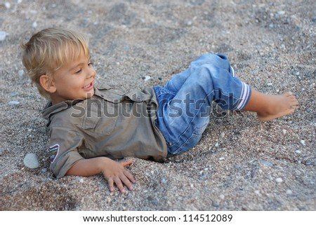 Child a little boy lying on sand and looking into the distance smiling