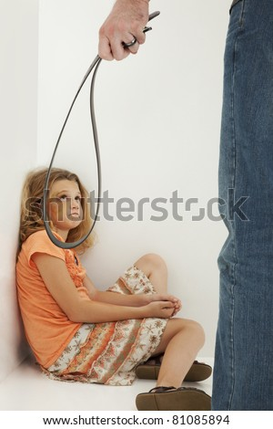 Child Abuse with abusive parent father and girl child in corner seen through belt.