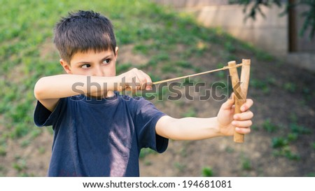 Child aiming with sling outdoors portrait. - stock photo
