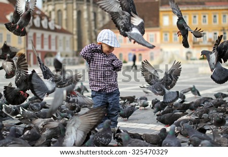 Child among doves in the city center - stock photo