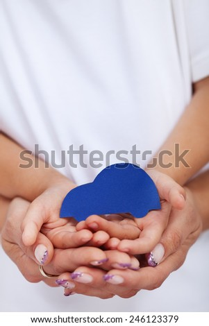 Child and adult hands holding car shaped paper - road safety concept - stock photo