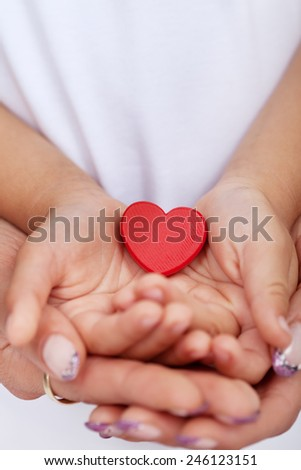 Child and adult hands holding red heart - love and care concept - stock photo