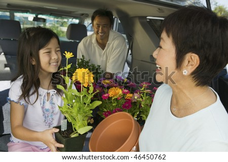 Child and Adults Loading Plants - stock photo