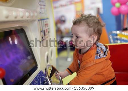 Child and amusement machine at indoor playground - stock photo
