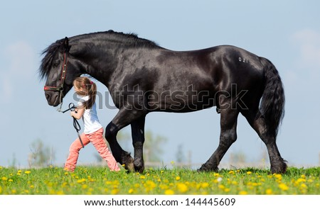 Child and big black horse in pasture in spring. - stock photo