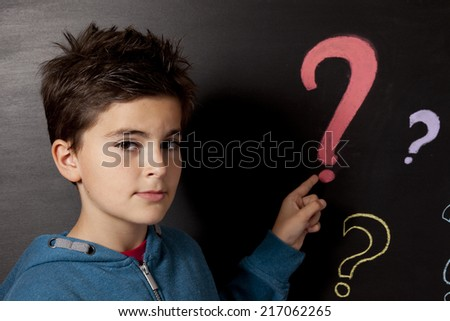 child and blackboard with questions mark - stock photo