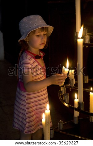 child and candle in the church - stock photo