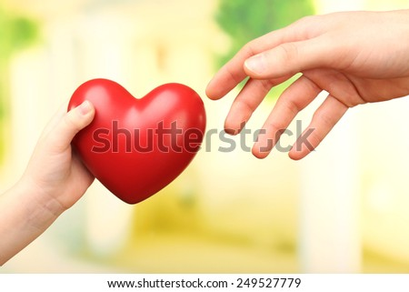 Child and father hands with heart on bright background - stock photo