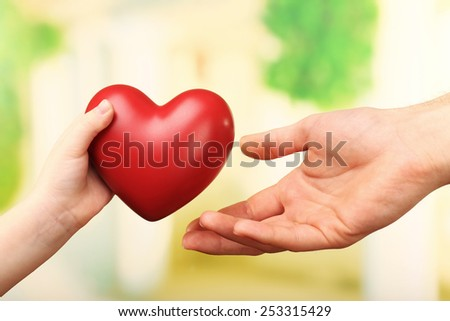 Child and father hands with heart on bright background