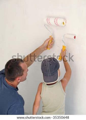 child and father painting wall together - stock photo