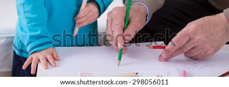 Child and grandfather coloring the image together - stock photo