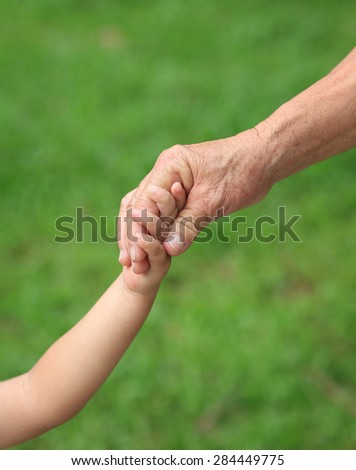 Child and grandma holding hands - stock photo