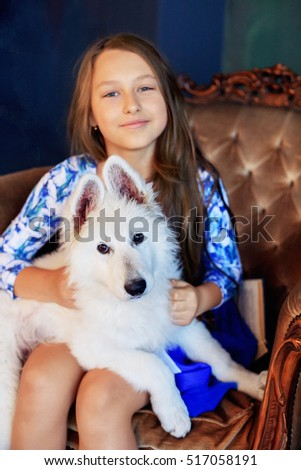 child and her dog sitting in a chair. The concept of friendship and lifestyle.